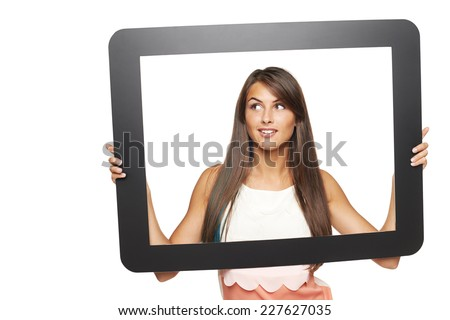 Smiling young woman looking to side through tablet frame, over white background - stock photo