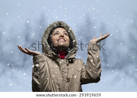 Smiling young woman looking up and enjoying snow fall - stock photo