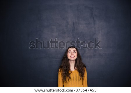 Smiling young woman looking up at copyspace over black background - stock photo
