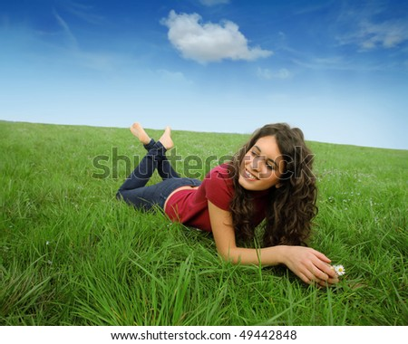 Smiling young woman lying on a green meadow - stock photo