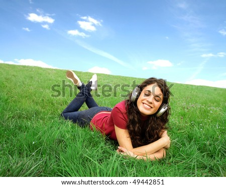 Smiling young woman lying on a green meadow and listening to music through headphones - stock photo