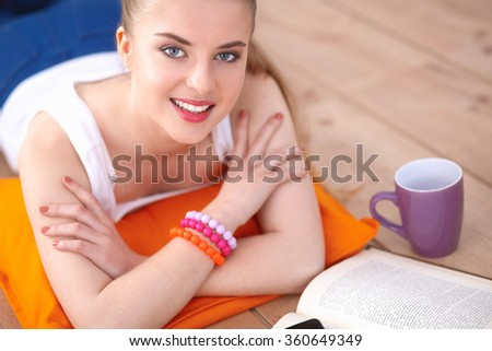 Smiling young woman lying on a white floor with pillow - stock photo