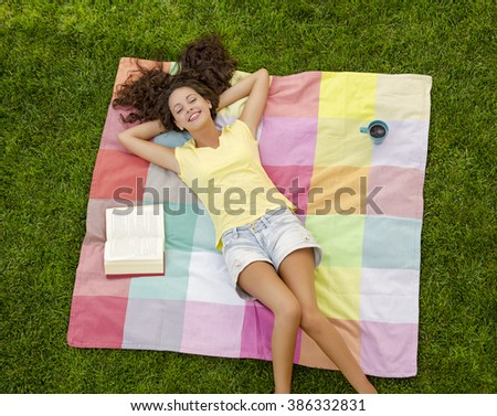 Smiling young woman lying on her back on a blanket and relaxing - stock photo