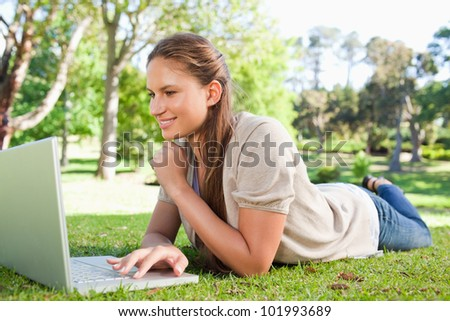 Smiling young woman lying on the lawn with her notebook