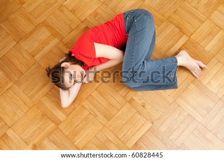 smiling young woman lying on the wooden floor
