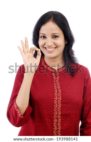 Smiling young woman making OK sign against white background - stock photo
