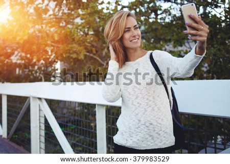 Smiling young woman making photo on mobile phone while standing on bridge near green tree in sunny day, joyful female student photographing herself on cell telephone during break between lectures - stock photo