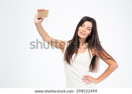 Smiling young woman making selfie photo on smartphone isolated on a white backgorund - stock photo