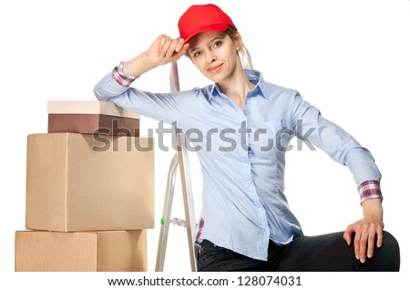 Smiling young woman near a pile of boxes on white background - stock photo