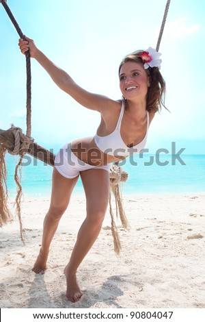 Smiling young woman on a beach playing  with swing - stock photo