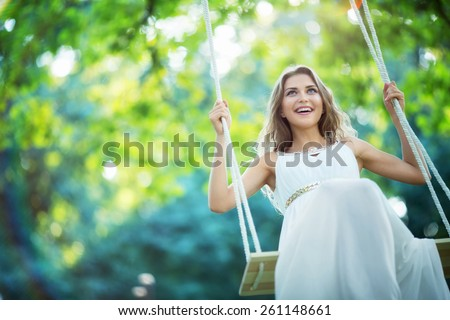 Smiling young woman on a swing - stock photo
