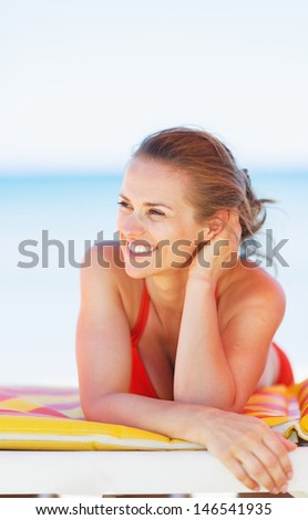 Smiling young woman on beach looking on copy space - stock photo