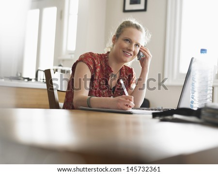 Smiling young woman on call writing notes at dining table - stock photo