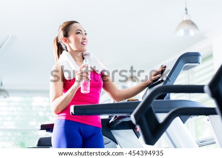 Smiling young woman on treadmill presenting water bottle as a reminder of sufficient hydration during workout - stock photo