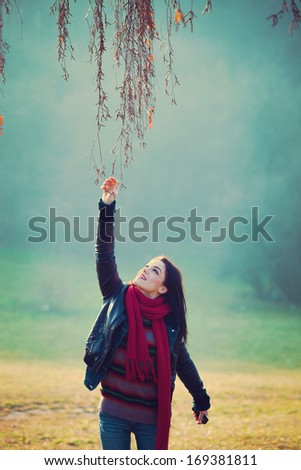 smiling young woman outdoor in park touch the branch  - stock photo