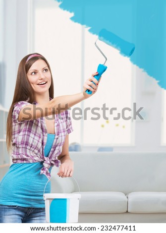 Smiling young woman painting the walls in her apartment with blue color paint  - stock photo