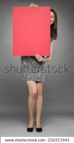 Smiling young woman peeping out through a red placard, gray background - stock photo
