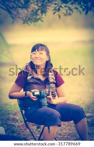 smiling young woman photographer holing DSLR camera in the camp travel mountain - stock photo