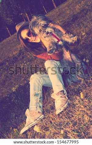 smiling young woman play with dog on meadow retro colors full body shot - stock photo