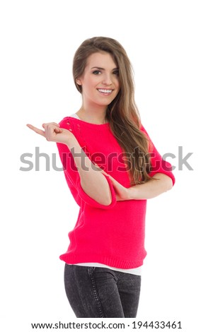 Smiling young woman pointing at empty space. Three quarter length studio shot isolated on white. - stock photo