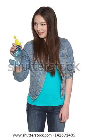 Smiling young woman pointing cleaning spray bottle to the side, against white background - stock photo