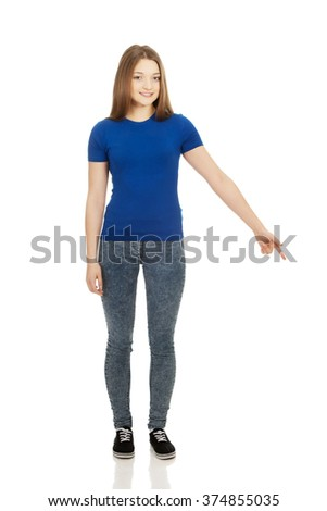 Smiling young woman pointing down. - stock photo