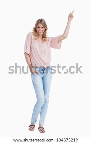 Smiling young woman pointing her finger against a white background