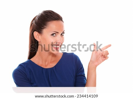 Smiling young woman pointing to her left while making a shooting gesture in white background - copyspace - stock photo