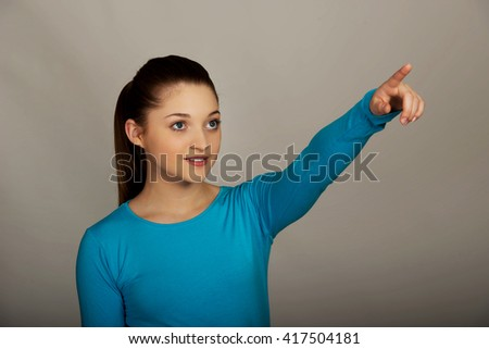Smiling young woman pointing up. - stock photo