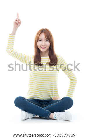Smiling young woman pointing upwards isolated on white background.