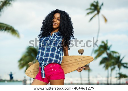 Smiling young woman portrait holding long board in South Pointe Park. South Beach Miami, Florida. - stock photo