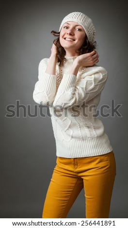 Smiling young woman posing in a studio wearing in a sweater and hat on gray background - stock photo
