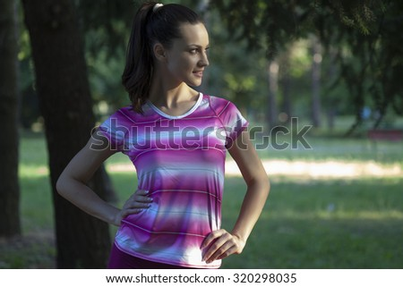 smiling young woman posing in the park