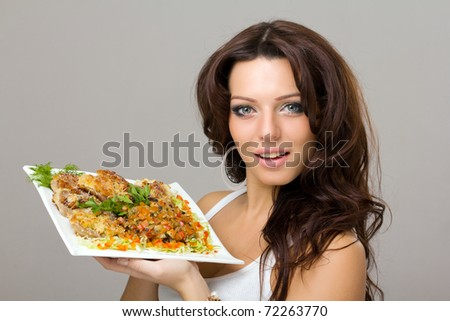smiling young woman posing with a meal on a gray background - stock photo