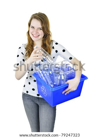 Smiling young woman putting plastic bottle into recycling box - stock photo