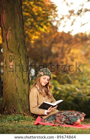 Smiling young woman reading a book in the park - stock photo