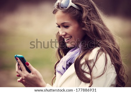 smiling young woman reading message on her smartphone outdoor shot - stock photo
