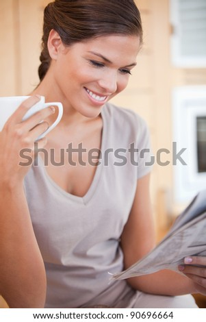 Smiling young woman reading newspaper while having tea - stock photo