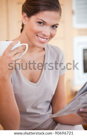 Smiling young woman reading the news while drinking coffee - stock photo