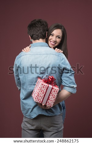 Smiling young woman receiving a beautiful gift with red ribbon from her boyfriend - stock photo