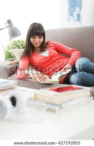 Smiling young woman relaxing at home on the couch and reading a novel, leisure and relaxation concept - stock photo
