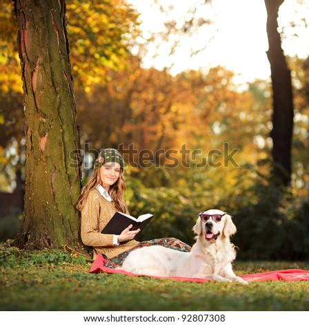 Smiling young woman relaxing in a city park with her labrador retriever dog - stock photo