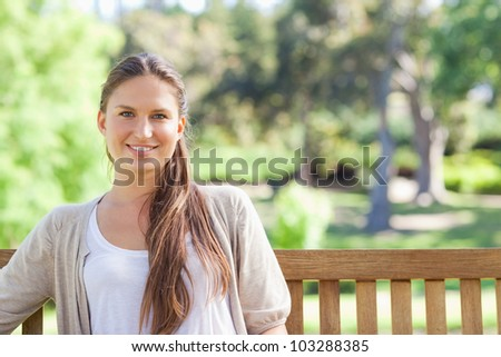 Smiling young woman relaxing on a park bench