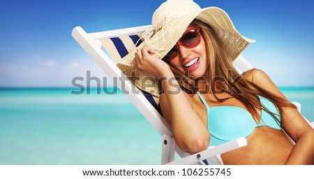 Smiling young woman relaxing on beach chair - stock photo