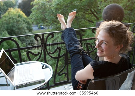 smiling young woman relaxing with a white modern laptop computer on a balcony in art nouveau - stock photo