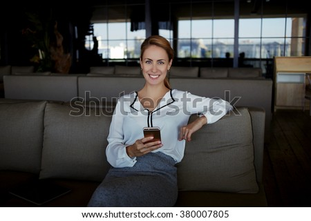 Smiling young woman restaurant owner holding mobile phone while waiting for a her clients, happy female dressed in elegant clothes posing with cell telephone while resting in cafe after hard work day - stock photo