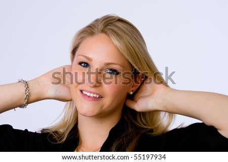 Smiling young woman runs her hands through her hair and looks at camera. - stock photo