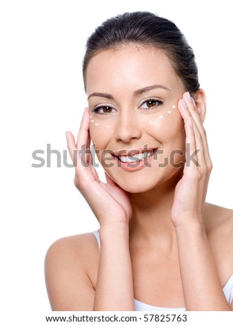 Smiling young woman's face with points of cream under the eyes - isolated - stock photo