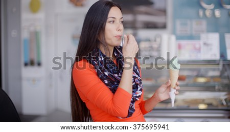 Smiling young woman savoring an ice cream cone - stock photo