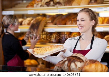 smiling young woman selling cake in bakery - stock photo